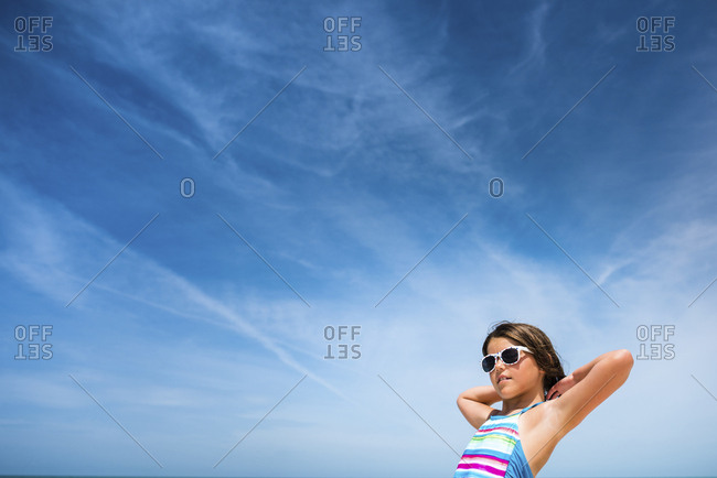Low angle view of girl in sunglasses against cloudy sky