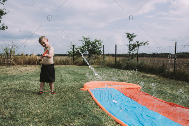 Boy playing with squirt gun by water slide at yard