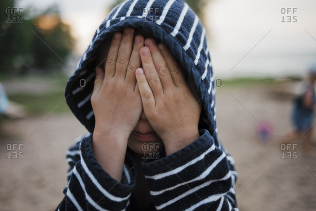 Boy in hooded shirt with hands covering face at beach