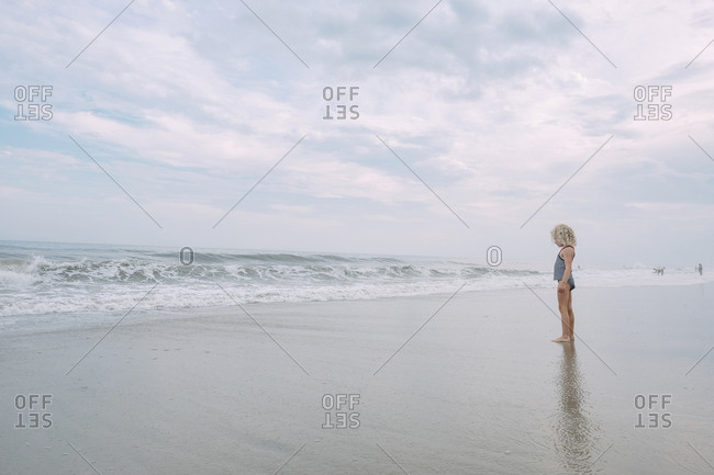 Full length of girl standing at Cape May Beach against cloudy sky