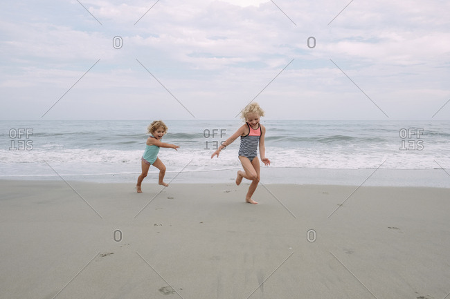 Happy sisters playing at Cape May Beach against sea and sky