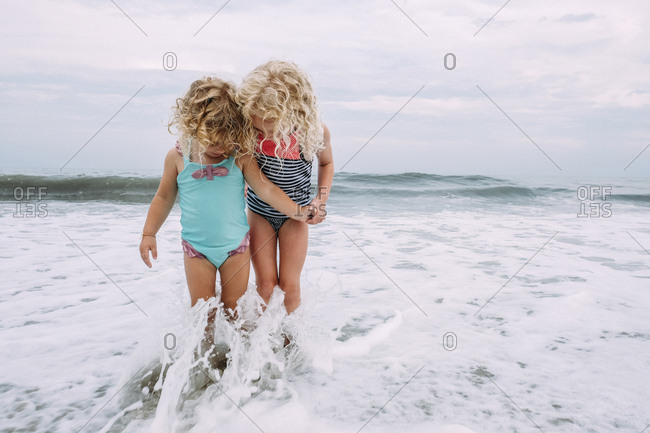 Sisters playing in waves at Cape May Beach against sky and sea