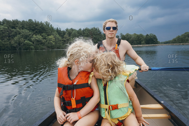 Sister kissing girl while father canoeing in lake against stormy clouds