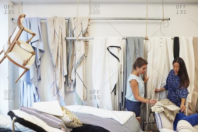 Interior designers selecting curtain samples in workshop