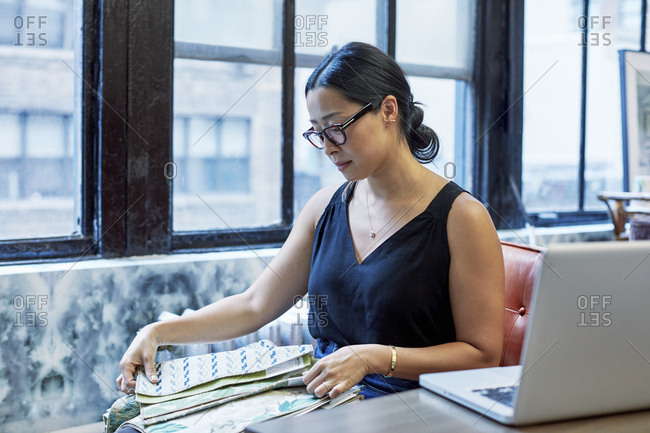 Interior designer looking at curtain samples while sitting against windows in workshop