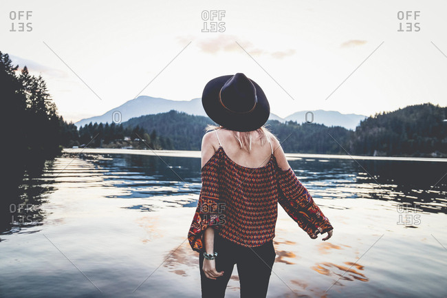 Rear view of woman if fedora hat looking at view while standing by lake during dusk