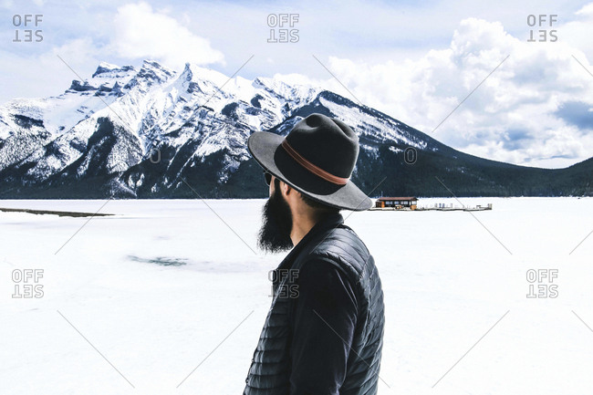 Rear view of man in fedora hat looking at view against cloudy sky