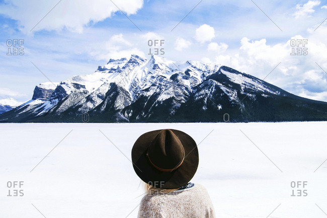 Rear view of woman in fedora hat looking at view against cloudy sky