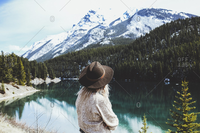 Rear view of woman in fedora hat looking at view by Lake Minnewanka