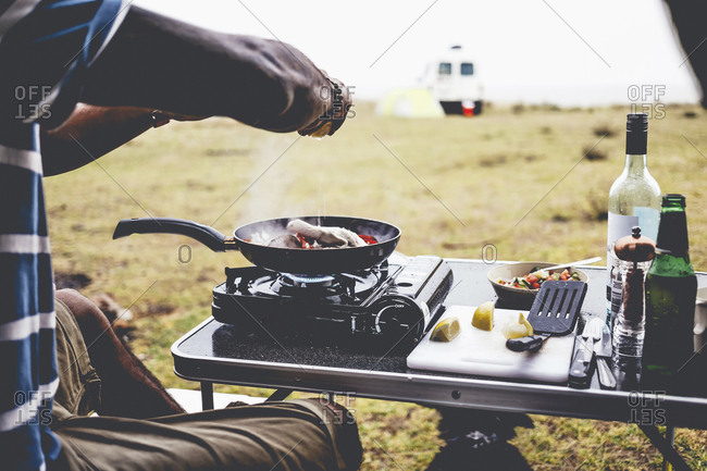 Cropped image of man preparing food on camping stove at campsite