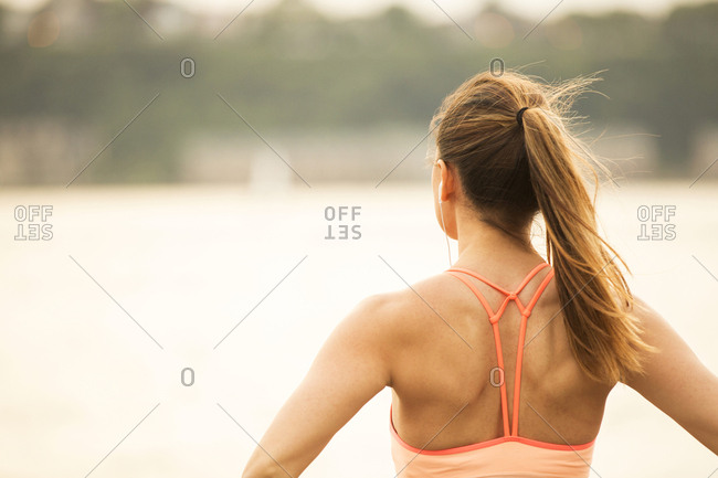 Rear view of thoughtful woman looking away while standing on bridge