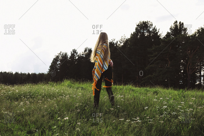 Rear view of woman in poncho standing on grassy field against clear sky