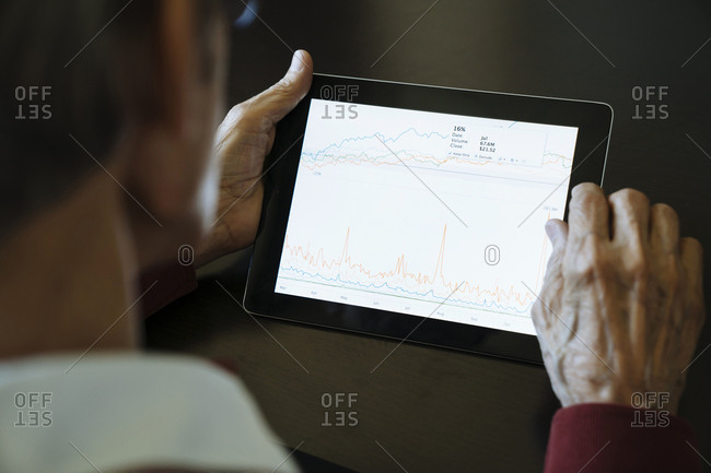 Cropped image of senior man studying graph on tablet computer in financial advisor's office