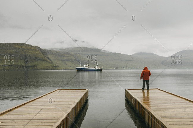 Rear view of man in hooded jacket standing on pier against mountains during foggy weather