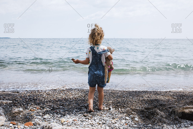 Rear view of girl with toy standing at beach against sea and sky