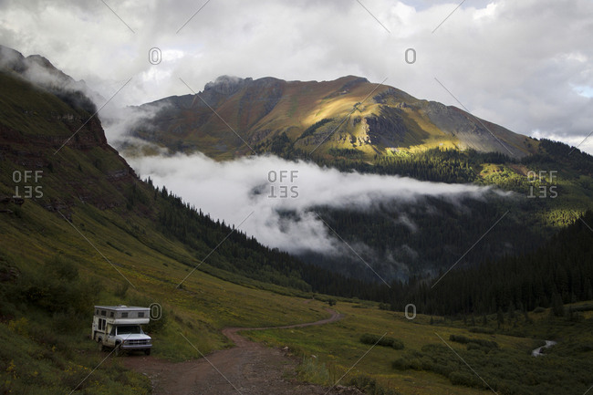 High angle view of travel trailer against San Juan Mountains during foggy weather