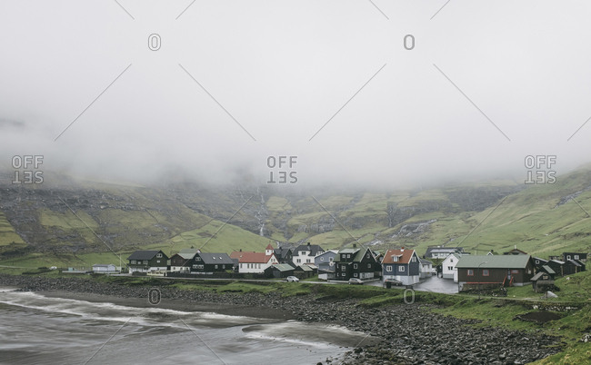 High angle view of village by sea during foggy weather