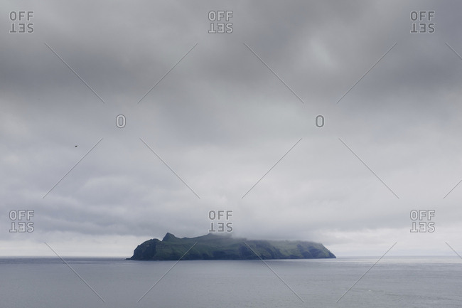 Island in sea against stormy clouds