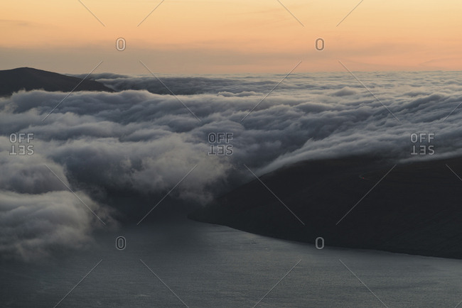 High angle view of islands in sea amidst clouds