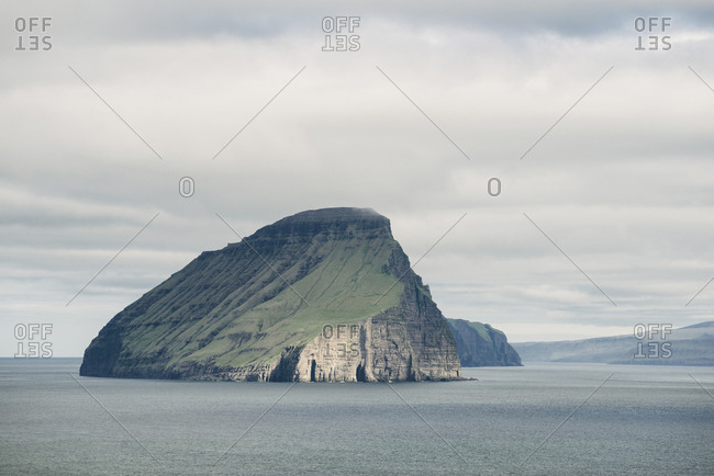 Idyllic view of island in sea against cloudy sky