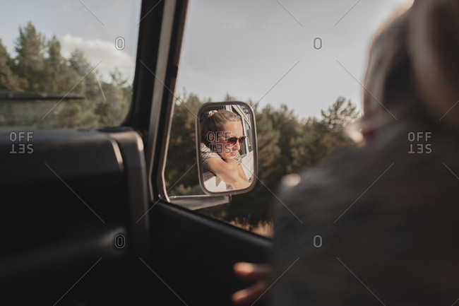 Reflection of woman seen in side-view mirror of car