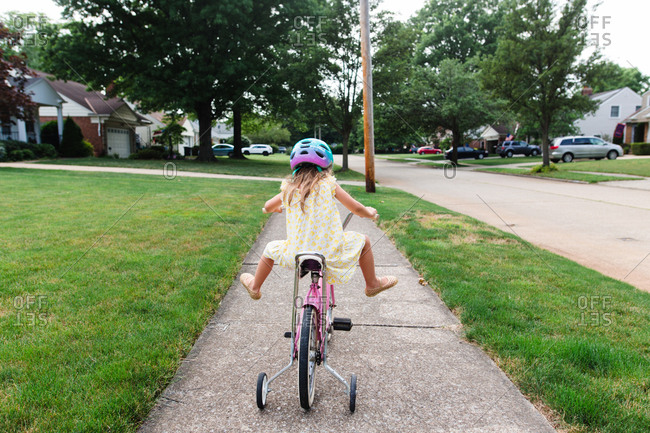 Little girl riding a bike on a sidewalk
