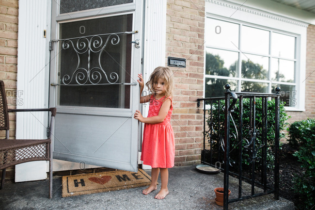 Little girl standing on front porch with open storm door