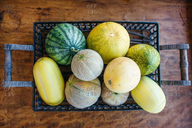 Melons in a basket on a wooden table
