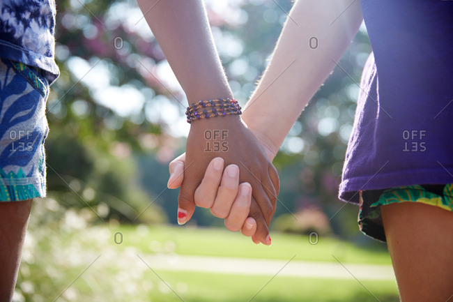 Close up of female couple holding hands