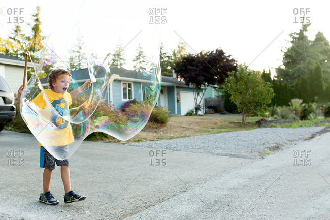 Boy making big bubbles outside
