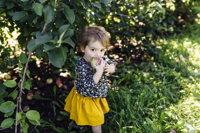 Girl biting apple standing outside