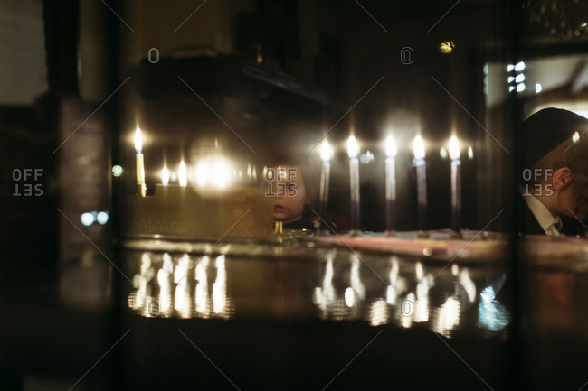 Child looking at lit menorah