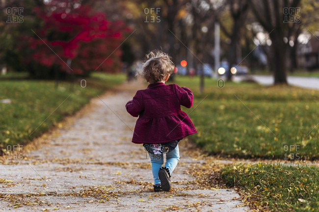 Toddler girl on sidewalk in fall