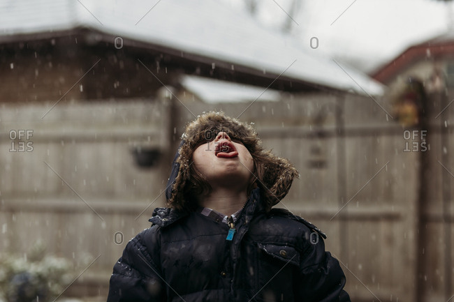 Child catching snow on tongue