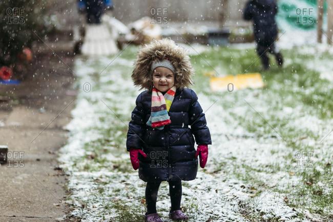 Girl standing in snowfall in yard