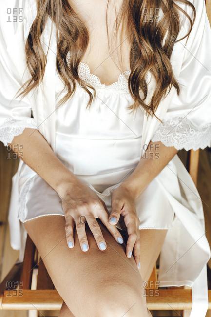 Close up of a bride hands on her legs