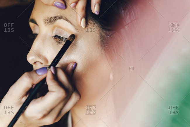 Make up artist putting eye shadow on bride's eyes for wedding ceremony
