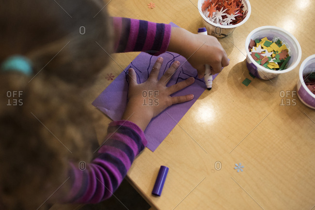 Little girl draws with a marker during arts and crafts