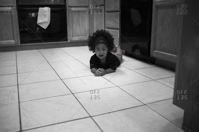 Toddler cries on the kitchen floor