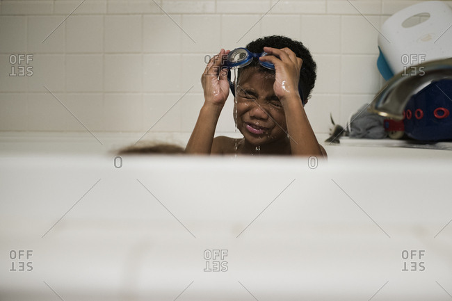 Boy takes a bath with goggles