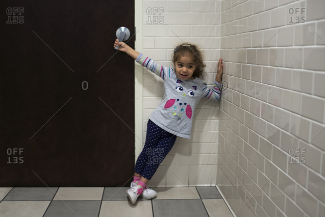 Toddler holds bathroom door handle