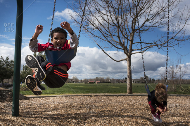 Boy and girl play on swing set