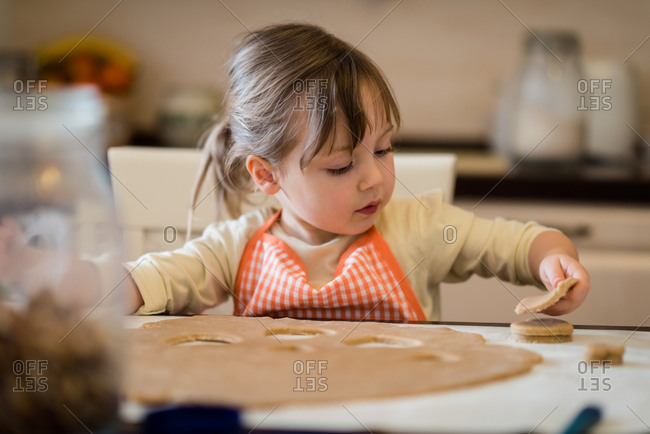 Girl child making cookies from fresh dough at home