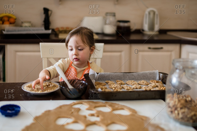 Kid placing cookies in oven tray ready to be baked