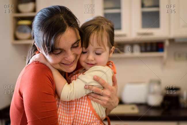 Cute girl child hugging her mother in kitchen