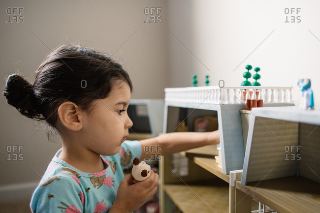 Little girl playing with toy animals and dollhouse