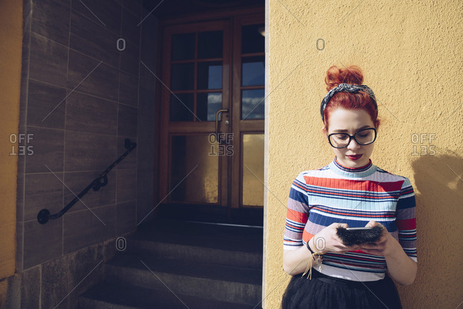Young female hipster using mobile phone while standing against wall by entrance of building