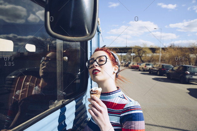 Young woman holding ice cream cone while standing by mini van on street