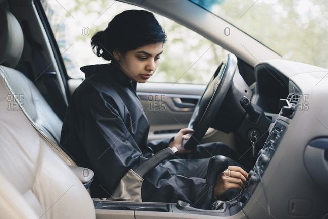 Female mechanic adjusting knob on dashboard in car