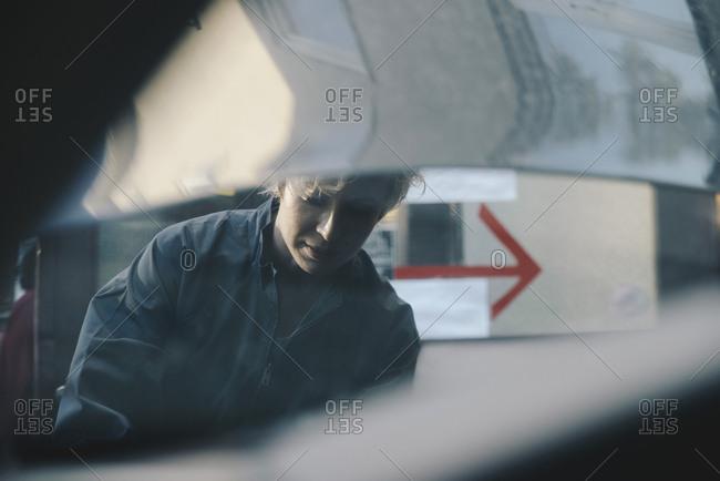 Female mechanic seen through open car hood